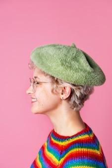 Vista laterale di una ragazza carina che indossa un maglione arcobaleno e un berretto verde su uno sfondo rosa