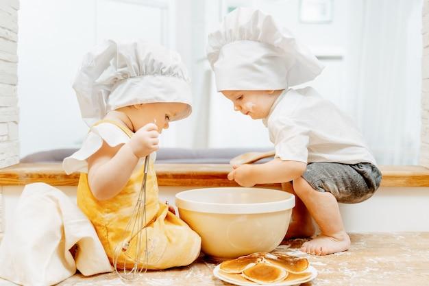 Vista laterale di simpatici ragazzi gemelli ragazzi e una ragazza in cappelli da cuoco preparare la pasta