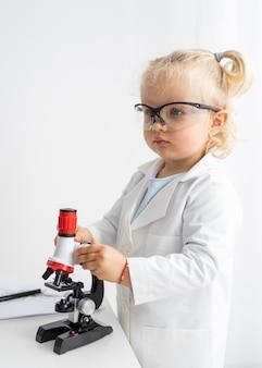 Vista laterale del bambino carino con microscopio e occhiali di sicurezza