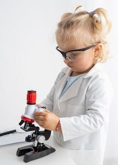 Vista laterale del bambino sveglio con il microscopio