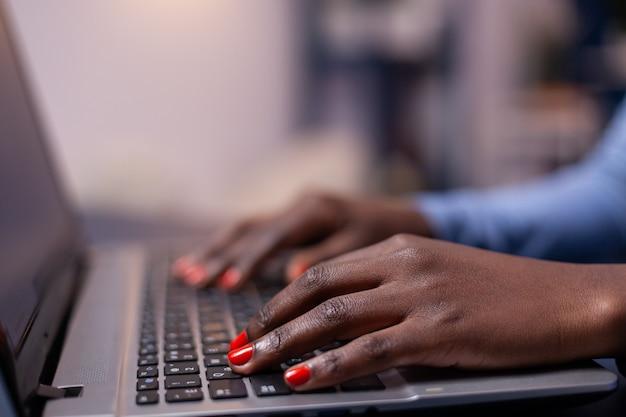 Vista laterale della donna d'affari dalla pelle scura che digita sul computer portatile seduto alla scrivania a tarda notte. dipendente che utilizza la moderna tecnologia di rete wireless facendo gli straordinari.