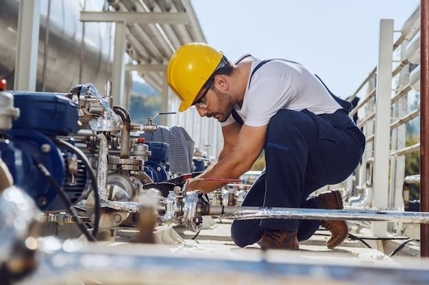 Vista laterale del lavoratore caucasico concentrato dedicato in tuta e con casco sulla testa in ginocchio sul serbatoio dell'olio e motore di fissaggio.