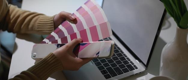 Vista laterale delle mani di designer che scelgono il colore dal campione di colore mentre si lavora con il laptop in ufficio a casa