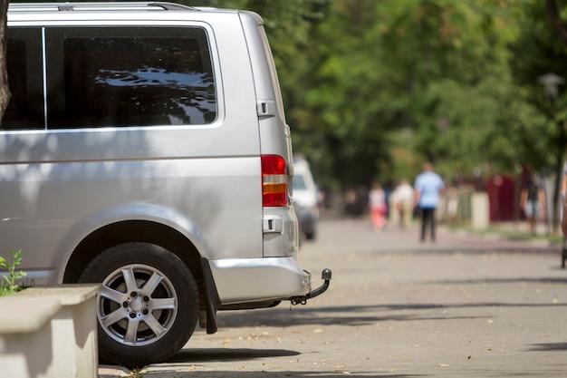 Il dettaglio di vista laterale del furgoncino di lusso del minibus del passeggero bianco di medie dimensioni ha parcheggiato sulla pavimentazione della via della città dell'estate Foto Premium