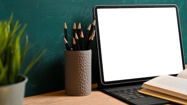 Vista laterale del modello dello schermo bianco della compressa digitale con il libro aperto, matite sopra il fondo verde della lavagna. torna al concetto di scuola