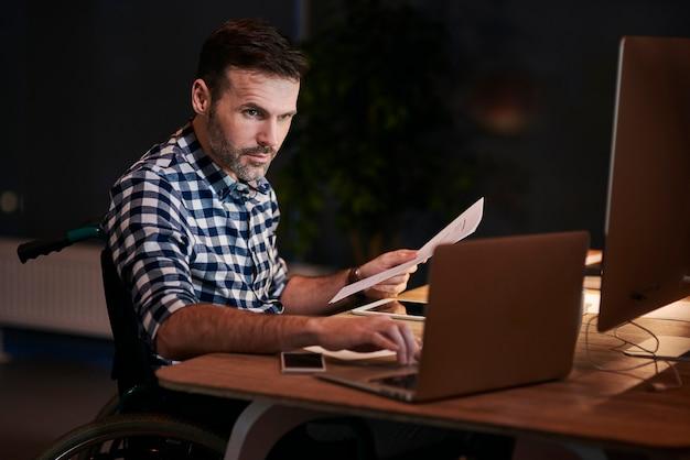 Vista laterale dell'uomo disabile con documenti che lavorano fino a tardi