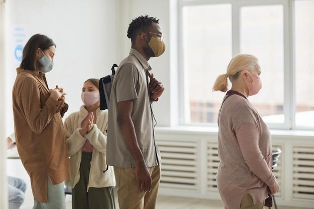 Vista laterale a diversi gruppi di persone che indossano maschere mentre aspettano in fila per registrarsi per il vaccino covid al centro di vaccinazione, copia spazio