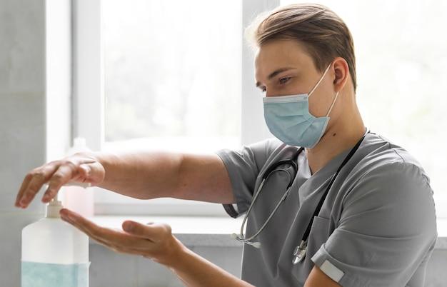 Vista laterale del medico con mascherina medica utilizzando disinfettante per le mani