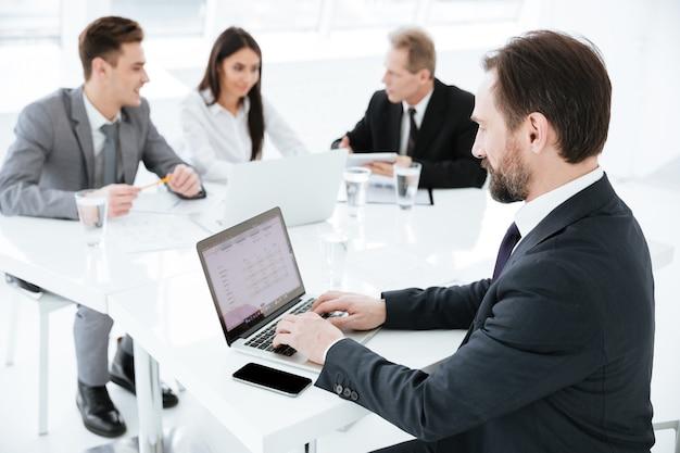 Vista laterale dell'uomo d'affari anziano seduto al tavolo con i partner commerciali e utilizzando il laptop in ufficio