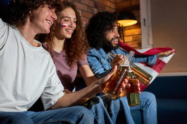 Vista laterale su amici eccitati che tintinnano bottiglie di birra durante la competizione di giochi sportivi in tv, tifo per la migliore squadra americana, anticipando l'obiettivo. concentrati sul ragazzo che ride