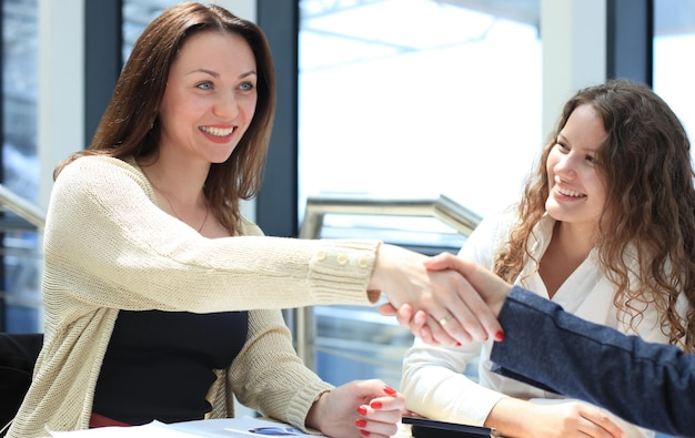 Vista laterale dei dirigenti che si stringono la mano durante un incontro di lavoro in ufficio