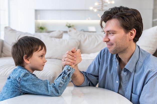 Vista laterale di padre e figlio in competizione a braccio di ferro