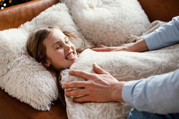 Vista laterale del padre che rimbocca la figlia a letto