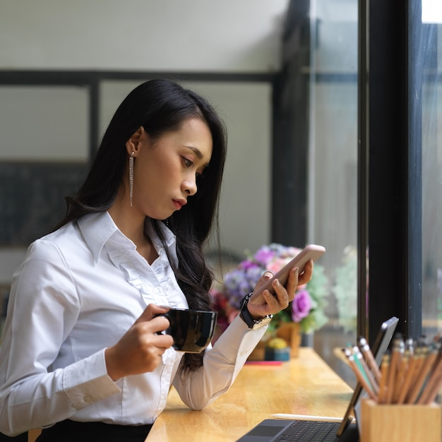 Vista laterale del feamle fare una pausa con lo smartphone e una tazza di bevanda mentre si lavora online nella caffetteria