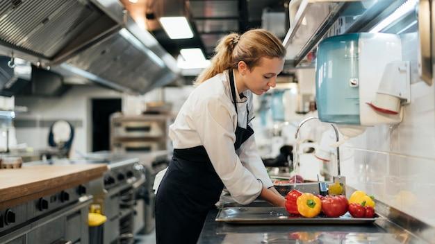 Vista laterale del cuoco unico femminile che lava le verdure