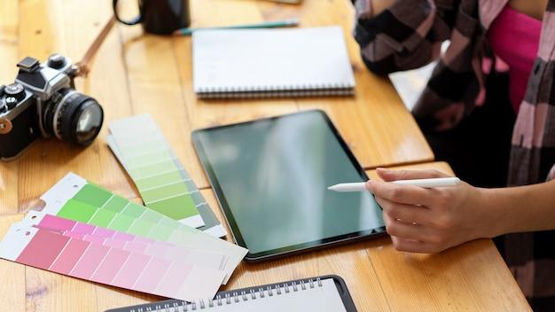 Vista laterale della studentessa designer che fa assegnazione con tavoletta digitale