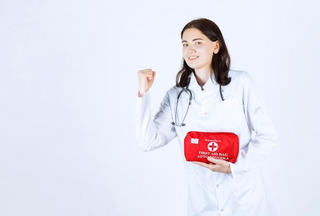 Vista laterale della dottoressa che stringe il pugno mentre tiene la sua borsa medica e sorride
