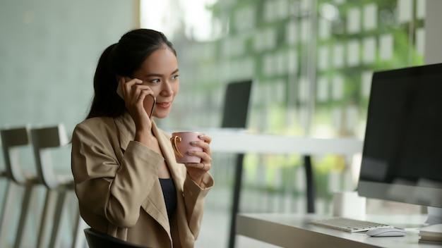 Vista laterale dell'imprenditore femminile che parla al telefono mentre fa una pausa nella stanza dell'ufficio della parete di vetro