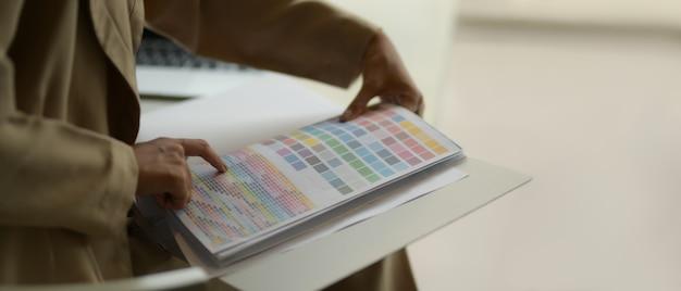 Vista laterale della stilista di moda femminile che sceglie il colore sulla cartella colori mentre era seduto nella stanza dell'ufficio