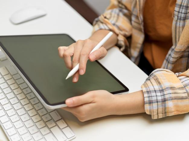 Vista laterale della libera professionista che lavora con la tavoletta digitale in ufficio a casa