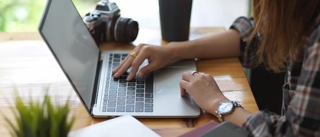 Vista laterale delle mani femminili che digitano sulla simulazione sulla tastiera del computer portatile sulla tavola di legno