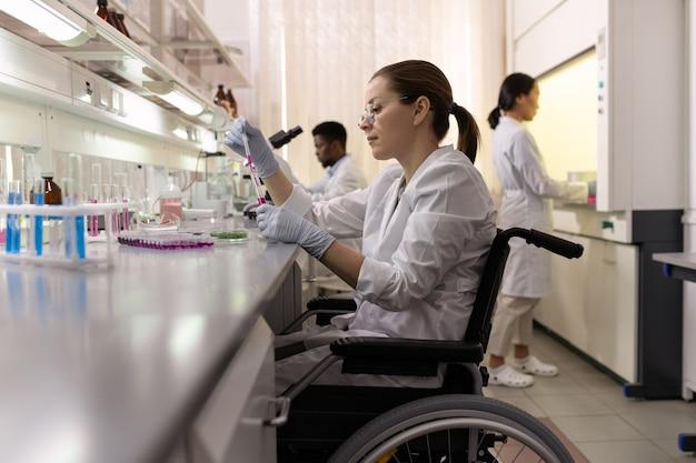 Vista laterale della lavoratrice di laboratorio in sedia a rotelle che sperimenta con i fluidi nelle boccette