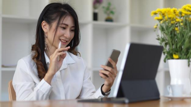 Vista laterale dell'impiegato femminile che tiene il suo smartphone