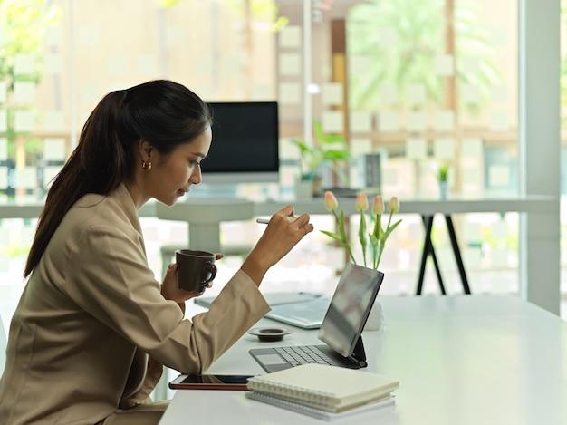 Vista laterale dell'impiegato femminile che lavora con la tavoletta digitale e che beve caffè nella stanza dell'ufficio