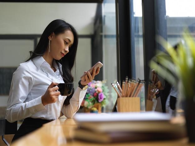 Vista laterale della donna rilassante con smartphone e tazza di caffè sul posto di lavoro