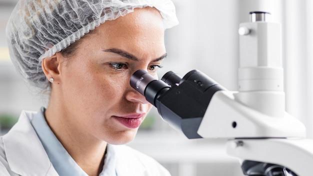 Vista laterale del ricercatore femminile nel laboratorio di biotecnologie con microscopio