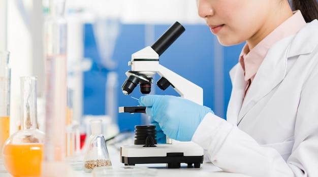Vista laterale della scienziata con i guanti chirurgici che guardano tramite il microscopio