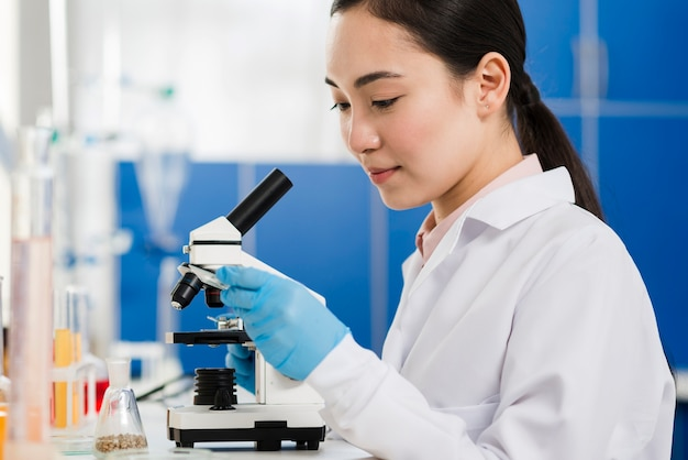 Vista laterale della scienziata con guanti chirurgici e microscopio