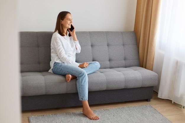 Vista laterale femminile seduta a parlare al telefono, ascoltando notizie piacevoli, indossando camicia bianca e jeans, trascorrendo del tempo a casa e comunicando con un amico.