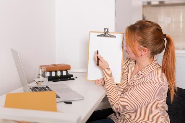 Vista laterale dell'insegnante femminile che mostra la lezione in linea