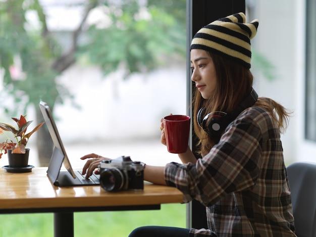 Vista laterale dell'adolescente femminile che beve bevanda calda mentre si utilizza la tavoletta digitale sulla barra nella caffetteria