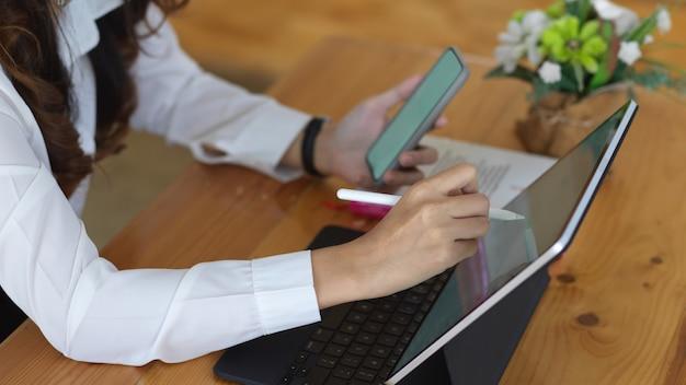 Vista laterale della donna che lavora con smartphone annuncio tablet sulla tavola di legno