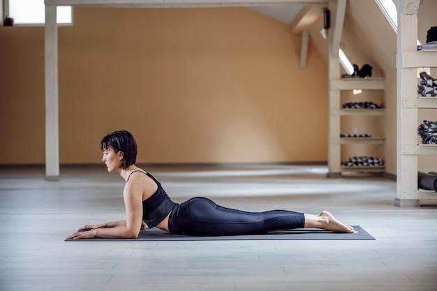 Vista laterale della donna in forma yogi con capelli castani in posa yoga sphinx. interiore dello studio di yoga.