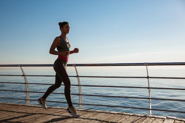 Vista laterale della donna fitness che corre lungo il lungomare