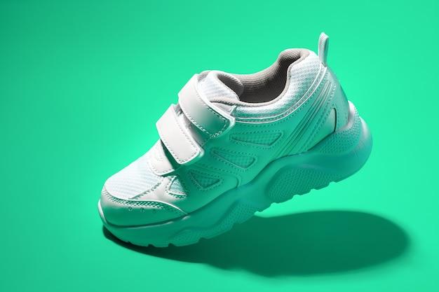 Sneaker bambino bianco volante vista laterale con chiusure in velcro isolate su uno sfondo verde con un duro ...