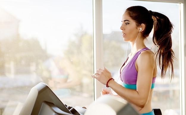 Vista laterale della ragazza di forma fisica giovane e persistente attraente concentrata che pratica sul tapis roulant nella moderna palestra soleggiata vicino alla finestra accanto a lei.
