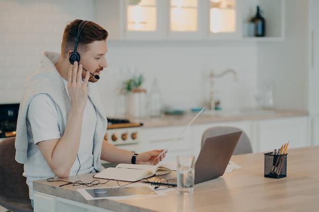 Vista laterale del gestore di chiamate barbuto focalizzato o del libero professionista seduto alla scrivania con il laptop in cucina moderna e guardando lo schermo mentre si fa una riunione online con il cliente. concetto di freelance