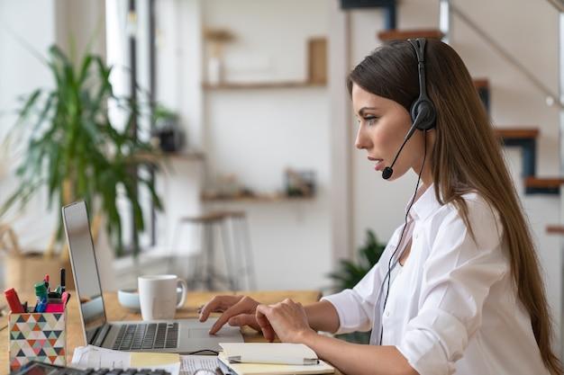 Vista laterale del chiamante concentrato o operatore telefonico receptionist in auricolari seduto al tavolo