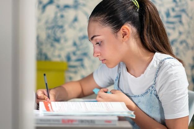 Vista laterale di una ragazza adolescente intelligente focalizzata che scrive nel quaderno mentre prepara i compiti a casa a tavola