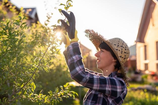 Vista laterale del giardiniere concentrato giovane donna caucasica taglia rami e foglie non necessari dall'albero