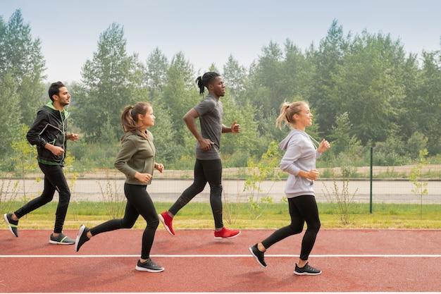 Vista laterale di quattro giovani sportivi e sportive che corrono lungo i circuiti mentre prendono parte a competizioni sportive