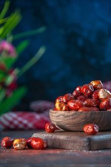 Vista laterale dei frutti freschi di silverberry crudi in una ciotola su un tagliere di legno su sfondo di colori misti