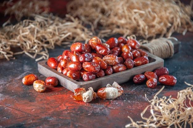 Vista laterale di frutti freschi di silverberry crudi all'interno e all'esterno di un vassoio di legno su sfondo di colori misti