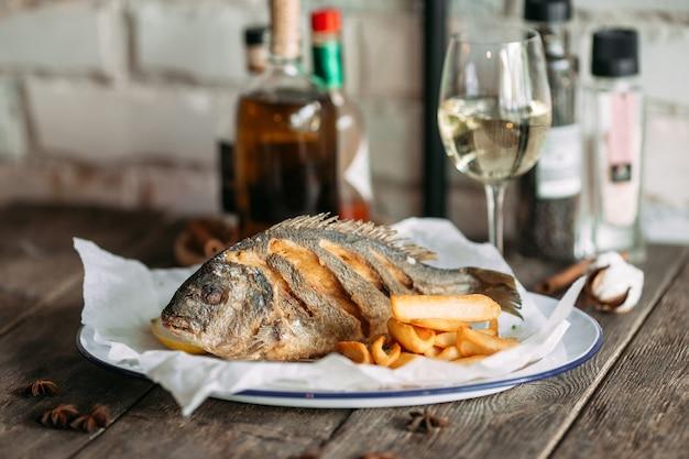 Vista laterale sul pesce dorado fritto con patatine fritte e vino bianco