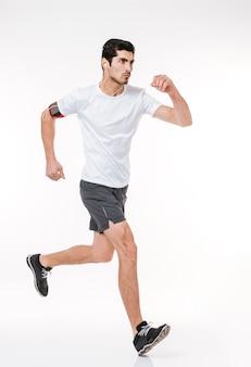 Ritratto a figura intera vista laterale di un giovane sportivo concentrato che corre con gli auricolari isolati su uno sfondo bianco