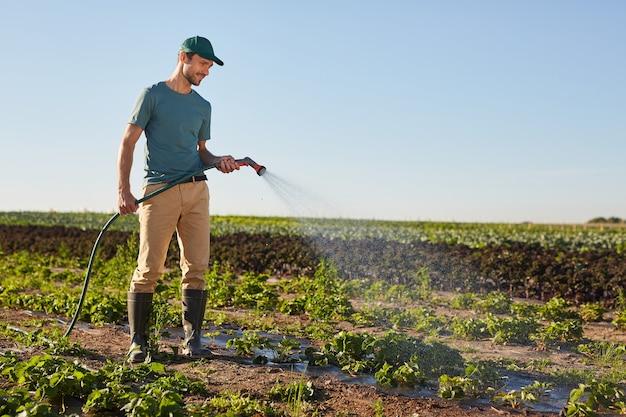 Ritratto integrale di vista laterale di giovane lavoratore maschio che innaffia i raccolti alla piantagione di ortaggi e sorride mentre levandosi in piedi all'aperto contro il cielo blu, lo spazio della copia